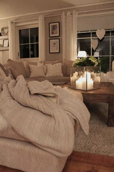 Cozy Living Area// I REALLY like that coffee table and the candle lantern thingy!  I dig the soft beige colors too!