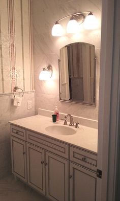 """Daltile Carrara 12x24 floor tile, 2x4 wall tile and tile used on wall behind mirror. Kichler Lighting """"Calleigh"""" in brushed nickel and """"Structures"""" mirror. Merillat Classic """"Lariat"""" maple vanity in Cotton with Tuscan glaze. Marble vanity top in """"Antique White"""""""