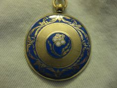 This is a gorgeous 9k gold locket/pendant with a locket compartment on the back. The front of this locket is enameled in a royal blue with a
