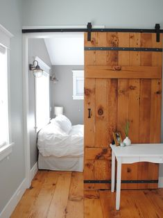 sliding barn door creates privacy for bedroom | natural wood contrasts the modern grey and white