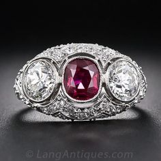 Few come finer than this ravishing ruby and diamond ring, exquisitely crafted in platinum. This gemmy vintage-style jewel centers on a bright, deep-red, oval cushion-cut ruby of Siam (Thai) origin, weighing one carat. The gorgeous gemstone rubs shoulders with a sparkling pair of European-cut diamonds weighing just shy of one carat each. The gracefully curved bombe-shape platinum mounting is lavishly ornamented in consummate Edwardian style with careful attention paid to each and every…