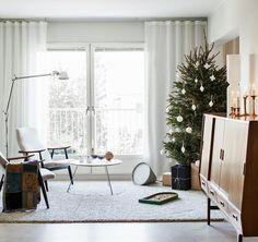 Kuusi on perinteisellä paikallaan olohuoneessa. Olohuoneen nurkassa on Tolomeo-jalkavalaisin ja lattialla betoninen Sektori-valaisin. Kehä-sohvapöytä on Matti Syrjälän suunnittelema. Lappalaisen nojatuolit on ostettu huutokaupasta  | HILLITTYÄ JUHLAA | Koti ja keittiö