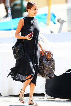 Nicole Richie was caught walking the pier on July 16th as she headed to the yacht she's sharing with Husband Joel Madden in Portofino. Richie wore a sheer black cover-up over a black and white striped bathing suit with studded gladiator sandals for the afternoon, while carrying a black hobo satchel and Goyard accessories for her Italian holiday.