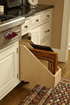 Slide out cutting board drawer in cabinet. Would also work for baking sheets and trays.