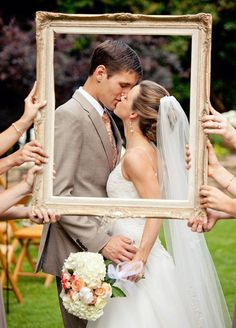 Capture a kiss! Everyone loves a good picture of the bride and groom sharing a kiss. Add a fun twist to a standard kissing picture by having your bridal party in the background of the photo.