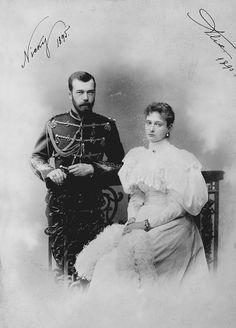 Nicholas II, Imperador da Rússia e Alexandra Feodorovna, Imperatriz da Rússia. Nicholas II está em pé à esquerda, vestindo uniforme militar e encostado em uma cerca de ferro forjado decorativo. Alexandra Feodorovna está sentado na frente da cerca à esquerda segurando um boá de penas. A fotografia é assinada e datada nos cantos superiores 'Nicky 1895' e 'Alix 1895'.