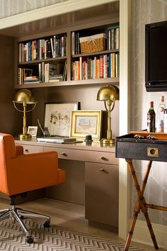 so much going on in this space in a good way.  love the brass lamps, campaign bar, built-ins and orange swivel chair.