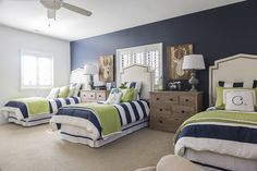 Though the house is large, Mark and Christin wanted the boys to share a bedroom. Neatly-made beds with striped duvets and lime green quilts line a wall painted in Benjamin Moore's Hale Navy. Tall headboards in white faux leather accented with brass tacks are stylish and practical.
