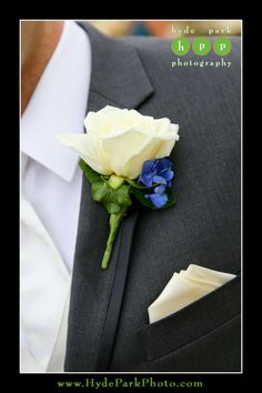 The groom's white rose boutonniere popped nicely against his charcoal grey suit, with just a touch of bright blue hydrangea. Photo by Austin Wedding Photographer Hyde Park Photography. Pearl Events | Villa Del Lago | RAE cosmetics | Bouquets of Austin | Michelle's Patisserie. @pearleventsatx  @raecosmetics  @bouquetsofatx  @mdoyon