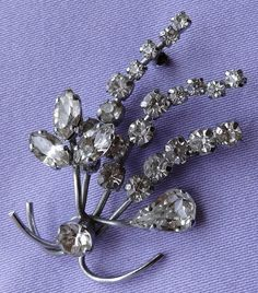 This fabulous brooch has a wonderful floral spray design. It has a silvertone metal frame adorned with sparkling round-cut, pear-cut and marquise-cut diamante stones.