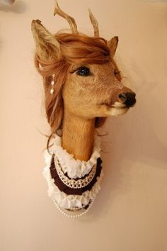 a taxidermy deer head with human hair wig and a lacey womens collar
