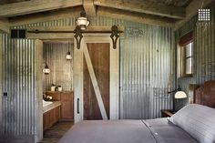 Locati Architects uses industrial metal on the walls of this bedroom to embody an old farm outbuilding. Photograph via Zillow