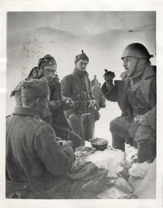 1941- Greek soldiers take time out for meal in snow-covered Tepelini sector of Albania during battle with Italians.