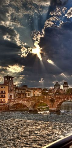 Light breaking through the dark clouds and shimmering on river, Ponte Pietra, Verona, Italy