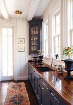 Love the dark wood worktops, grey cabinets, white weatherboarding and runner