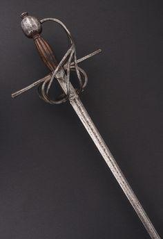 """R-109AG.-  Espada ropera con guarnición de lazo. España - Valencia, hacia 1600-1630. Bella guarnición en hierro, formada por una cruz de gavilanes rectos con escusón central, patillas, guarda de dos puentes, ramas en la contraguarda, recazo, guardamano y gran pomo facetado con perilla. Puño de madera. Hoja recta, en ambos costados el recazo presenta tres punzones de armero y el vaceo la inscripción """"IN VALANCIA"""". Long. Total: 118,5 cm; Long.Hoja : 104 cm; Anchura base hoja: 21 mm"""