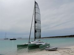 Dragonfly 28 trimaran sails right up to the beach, leaving other boats anchored off in the deep water