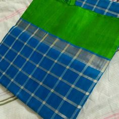 Kuppadom blue color checked silk saree with green border.