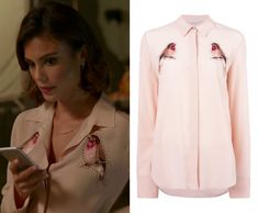 """Cristal Flores (Nathalie Kelley) wears this light pink bird embroidered blouse in this episode of Dynasty, """"Company Slut"""". It is the STELLA MCCARTNEY embroidered robin crystal shirt."""