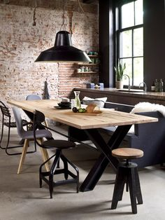 Gravity Home: Industrial kitchen and dining space with exposed brick