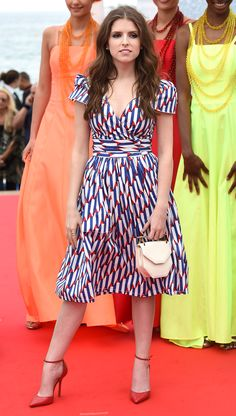 2016 Cannes: Anna Kendrick is wearing a red, white, blue Marc Jacobs short sleeve wrap dress with a cinched in waist. The dress is adorable! Perfect for France! I like the red ankle strap pumps to go with the red in the dress.