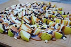 APPLE NACHOS:  4 large Granny Smith apples, sliced; 35 large marshmallows; 1/4 cup butter; 35 caramels; 1 Tbsp evaporated milk (or half and half); 1/4 cup peanuts; 1/4 cup mini semi-sweet morsels; 2 Tbsp chocolate syrup