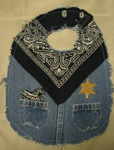 This is a cute boys cowboy western bib. It is made with recycled jeans and a blue bandana handkerchief. It has little pockets with a small