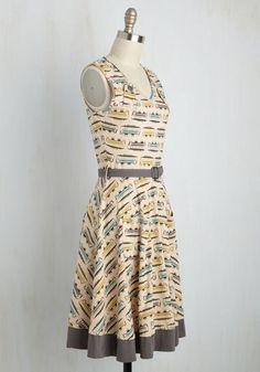 The train into town is full of fun characters, and this stretch cotton dress by Cali-based Effie's Heart only adds to yours! Anything but bland, this belted, beige dress flaunts a lime, grey, and blue trolley print, buttoned accents at the shoulders, and patch pockets that culminate in a personality-filled appearance.
