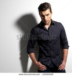 Fashion portrait of young man in black shirt poses over wall with contrast shadows by Valua Vitaly, via Shutterstock