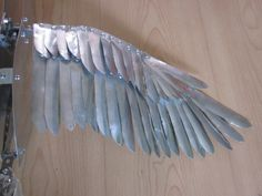 wing from a bird puppet, featuring rivets and metal feathers
