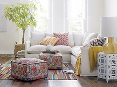 Love the white walls, sofa and geometric table. Love the same pillow pattern in different colors, but don't think need both poufs. Hate the rug in this room - too much color and busy pattern. Crate & Barrel