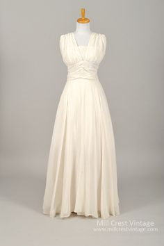 Designed in the 50's, this beautiful vintage wedding gown is done in a poly chiffon over an acetate lining. The sleeveless bodice offers a lace insertion un...