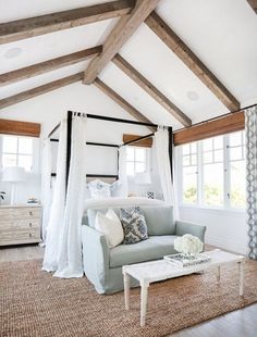 California beach house master bedroom with exposed beams, vaulted ceilings and breezy blue and white decor.