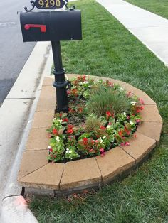 Simple stone border around mailbox + colorful annual flowers