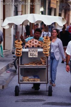 Street vendor pushing his stand and selling donuts, breads and pastries - Rethymno, Rethymno Province, Crete