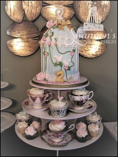 "I love this ""Tea for Two"" concept for a little girl's 2nd birthday! The top tier of the display is a fondant covered birdcage cake in theme colours of aqua, pink, gold, and white. Cupcakes have butterfly, bow, and flower fondant accents. Some of the cupcakes are displayed in tea cups! Cupcakes are chocolate / cream cheese and vanilla / cotton candy. Cake is marble with Nutella buttercream filling and white chocolate ganache frosting."