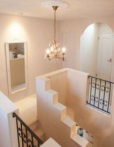ホワイトカラーの階段ホールに、ゴールドのシャンデリアと黒いアイアン手摺。|おしゃれ|ライト|自然素材|