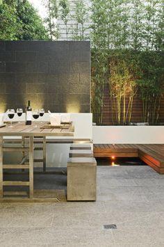 Este increíble jardin tiene una zona para comer, un mini fogón, una fuente de agua, asientos en obra con espacio para almacenamiento y un quincho empotrado