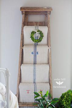 Christmas decor using grain sacks on a vintage ladder from cedarhillfarmhouse.com