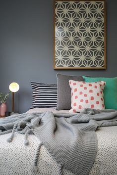 Grey feature wall, blue and white linen, pink, turquoise, paper artwork, guest bedroom