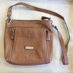 "Brown leather crossbody bag Light brown cross body bag. Has outside zipped pocket as well as a magnetic closure pocket with lots of card pockets and a zipped pocket. Inside has two open pockets and a zipped pocket. Overall purse zips. Brand is Tignanello since 1989. Hardware is silver. 100% leather body and 100% polyester lining. Measures 11.5"" tall and 12.75"" wide. Maximum of 5"" deep. Strap is 22"" from top of purse. Few minor scratches and some wear on bottom corners. Strap has areas where…"