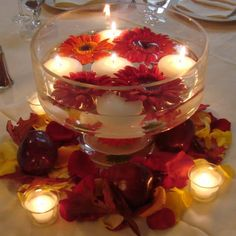 Maybe lots of floating candles and a few flowers in a bowl for the tables in the grass? With votives and ornaments and or bead garland around the base on the table?