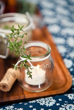simple adornments of herbs tied with baker's twine around repurposed glass containers for candle votives