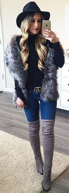 Gray faux fur vest over black top and blue jeans with gray OTK boots.