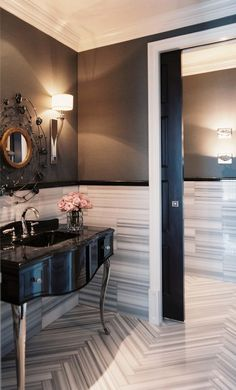 bath with marble striped lower walls and charcoal painted upper walls, black pocket door, elegant vanity on legs