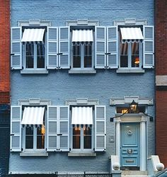 Miles Redd... his beloved blue front door. Brick paint is actually pale grey, door is laquered pale blue, awnings are grey & white striped, hardware is polished silver. Yum.