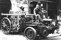Battalion Chief Wesley Williams riding an old fire truck. unknown location and year.
