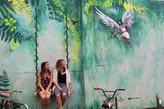 MillieNewitt Interactive Mural in Tauranga, New Zealand. The viewer sits on a swing to become a part of this forest scene, ready to be shot by a modern day cupid's arrow.