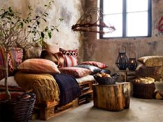 Stained walls and old wood, pallet beds and crocheted quilts, wrought iron and green leaves.