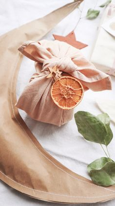 A Christmas gift wrapped in an avocado dyed piece of natural cotton tied in the furoshiki way, decorated with a dry orange slice and wooden stars. Christmas Candles, Christmas Love, Christmas Gifts, Christmas Oranges, Christmas 2019, Wrapping Ideas, Creative Gift Wrapping, Dried Orange Slices, Dried Oranges